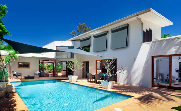 Photo of Fixed Guide Awnings shading windows overlooking a pool