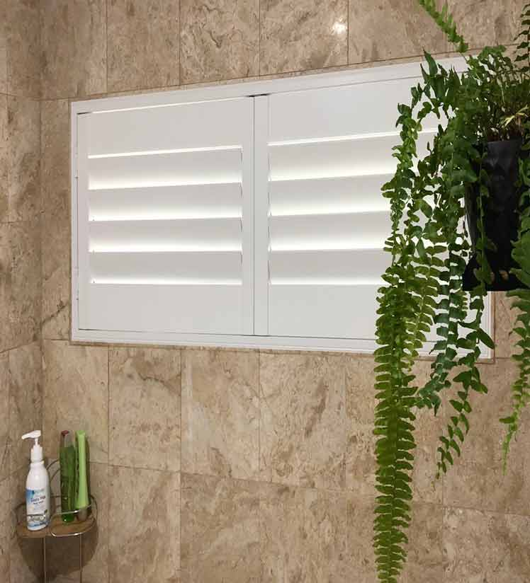 Hinged plantation shutters fitted in a bathroom