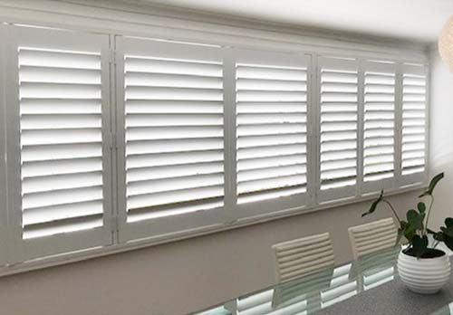 White plantation shutters fitted for a dining room