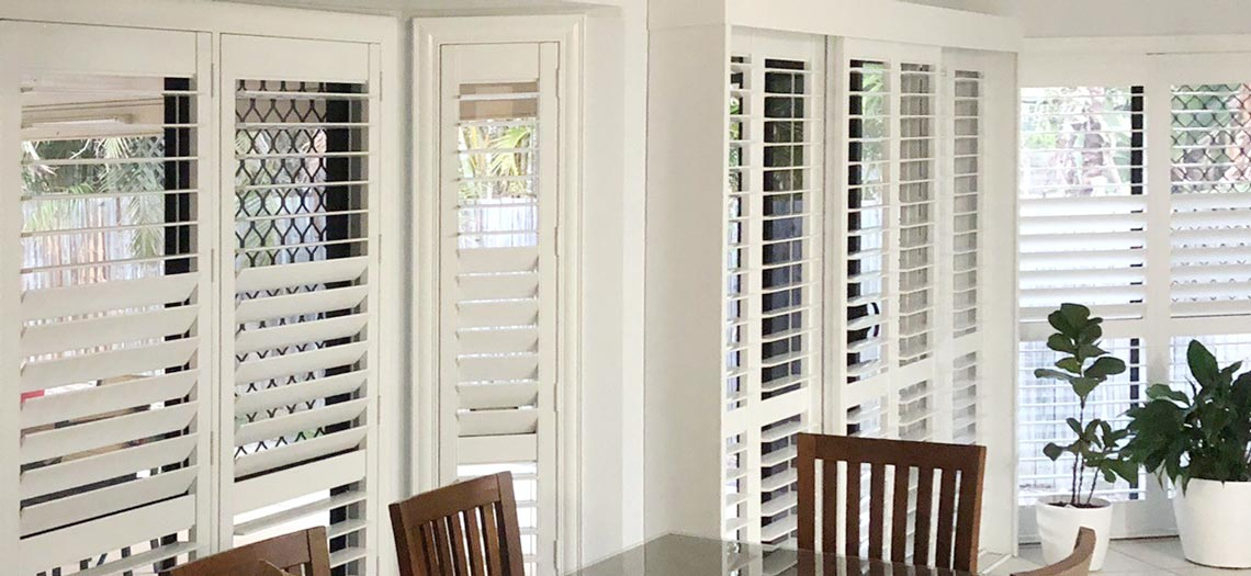 Hinged plantation shutters fitted in a living room