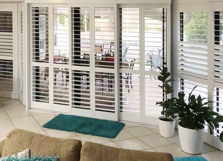 Sliding plantation shutters fitted in a living room