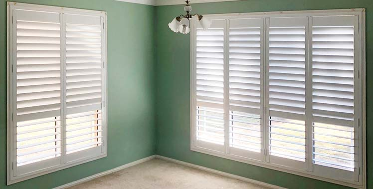 Hinged plantation shutters fitted in a bedroom