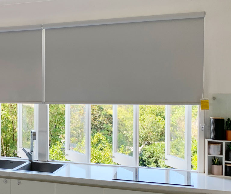 Soft Grey roller blinds fitted to casement windows