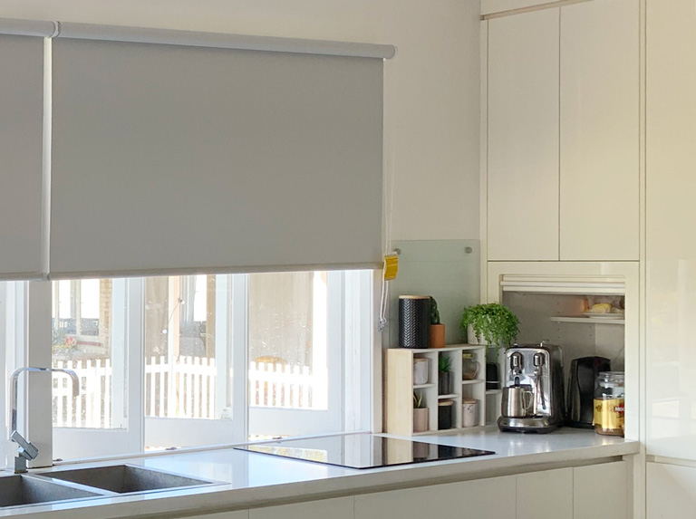 Soft Grey roller blinds fitted to kitchen casement windows