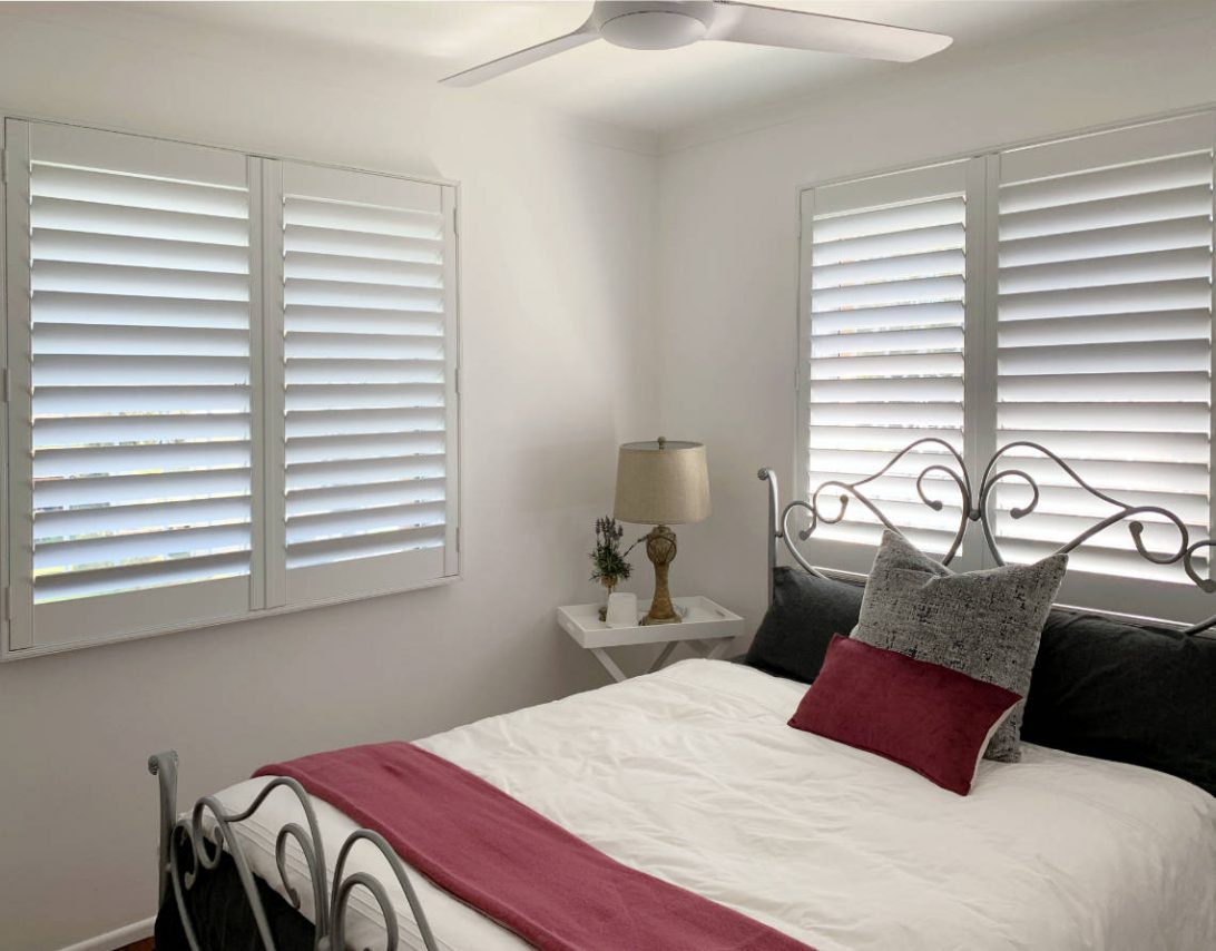 White plantation shutters for a bedroom window